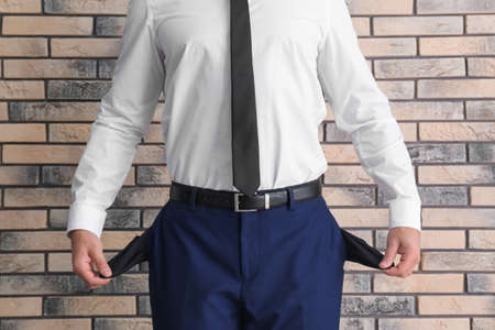 Businessman showing empty pockets near brick wall, closeup