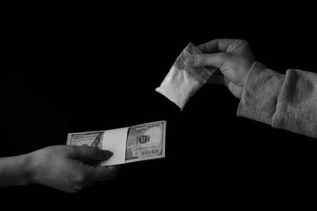 Drug dealer selling cocaine to addict on black background, closeup Stock Photo