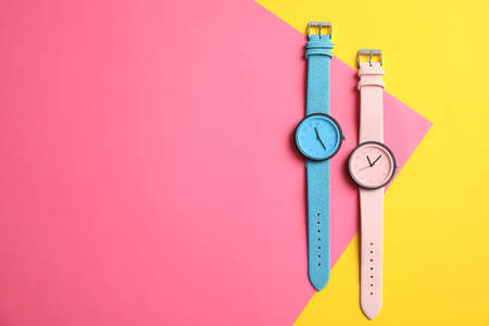 Flat lay composition with stylish wrist watches and space for text on color background. Fashion accessory