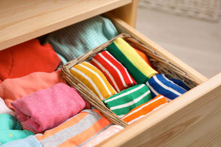 Many different colorful socks in open drawer, closeup