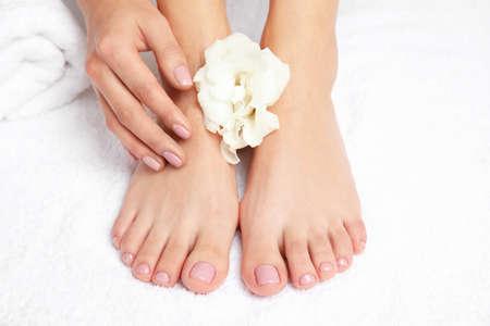 Frau, die ihre glatten Füße auf weißem Tuch, Nahaufnahme berührt. Spa-Behandlung Standard-Bild
