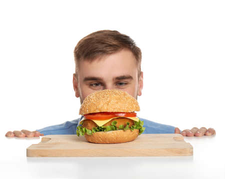 Young man and tasty burger on white background Banco de Imagens