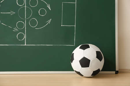 Soccer ball near chalkboard with football game scheme on table Stockfoto