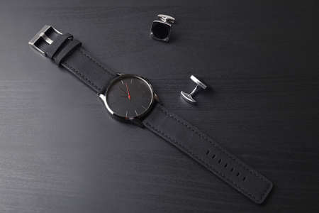 Stylish wrist watch and cuff links on dark table. Fashion accessory Reklamní fotografie