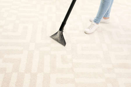 Woman removing dirt from carpet with vacuum cleaner indoors, closeup. Space for text