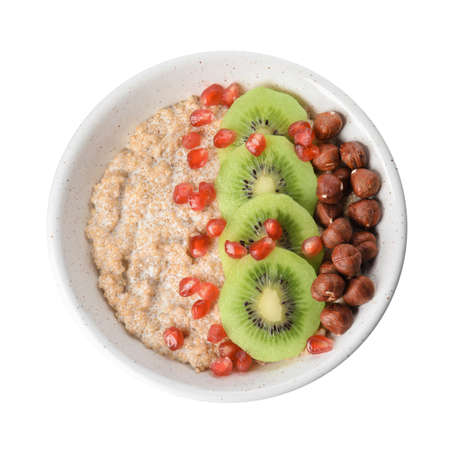Bowl of quinoa porridge with hazelnuts, kiwi and pomegranate seeds on white background, top view