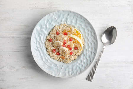Plate of quinoa porridge with orange, banana and pomegranate seeds near spoon on white wooden background, top view