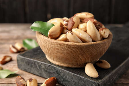 Wooden board with bowl of tasty Brazil nuts on table Фото со стока