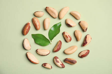 Flat lay composition with Brazil nuts and leaves on color background Stockfoto
