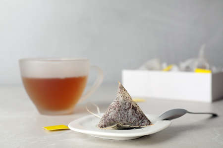 Saucer with used tea bag on table