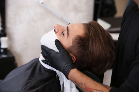 Professional hairdresser using cold towel to calm client's skin after shaving in barbershop 免版税图像