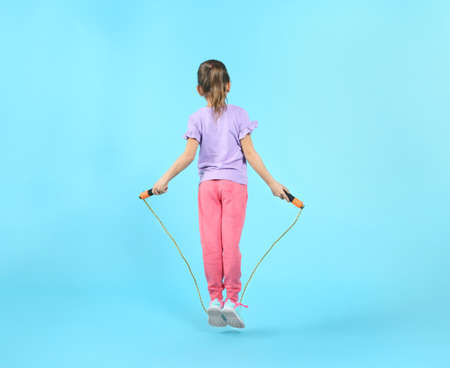 Active girl jumping rope on color background Stock Photo