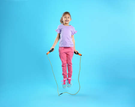 Full length portrait of girl jumping rope on color background