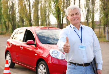 Senior instructor near modern car outdoors. Get driving license