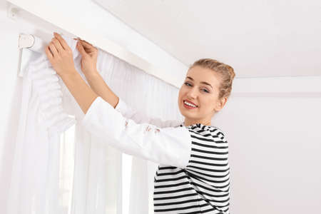 Woman hanging window curtain indoors. Interior decor element Banque d'images