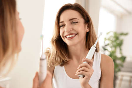 Young beautiful woman with toothbrush near mirror in bathroom. Personal hygiene Banque d'images - 116292034