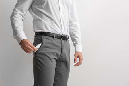 Businessman showing empty pocket on light background, closeup. Space for text