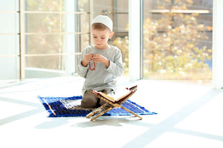 Little Muslim boy with misbaha and Koran praying on rug indoors