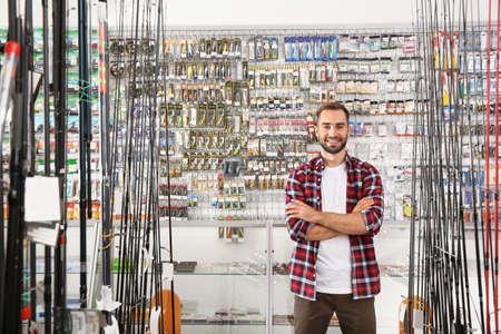 Homme debout près d'une vitrine avec du matériel de pêche dans un magasin de sport. Espace pour le texte Banque d'images