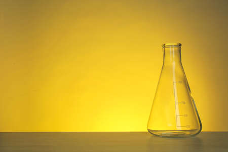 Conical flask with liquid on table against color background. Chemistry laboratory glassware