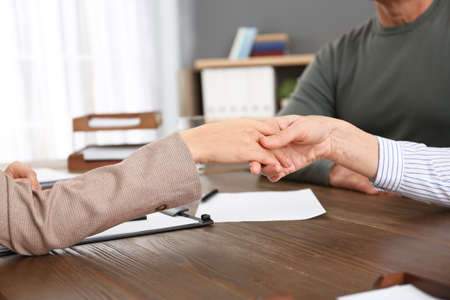 Lawyer shaking hands with client in office, closeup Reklamní fotografie