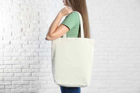 Woman with eco bag near brick wall. Mock up for design
