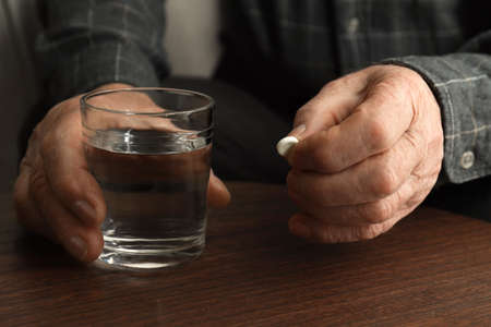Senior man holding pill and glass of water at table, closeup 版權商用圖片