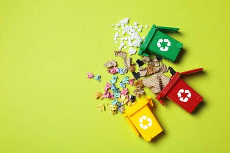 Cubos de basura y basura diferente sobre fondo de color, vista superior con espacio para texto. Concepto de reciclaje de residuos