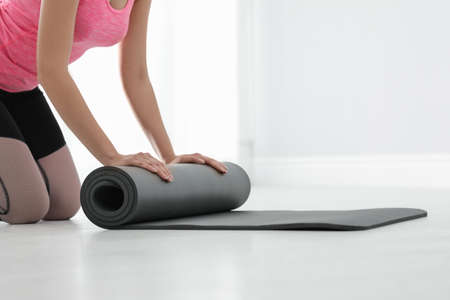 Young woman rolling yoga mat indoors, closeup. Space for text