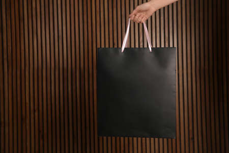 Woman holding paper shopping bag on wooden background. Mock up for design 스톡 콘텐츠 - 114511529
