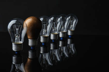 One different light bulb among others on black background Stock Photo