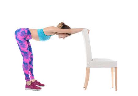 白い背景に椅子を持って運動する若い女性。ホームフィットネス
