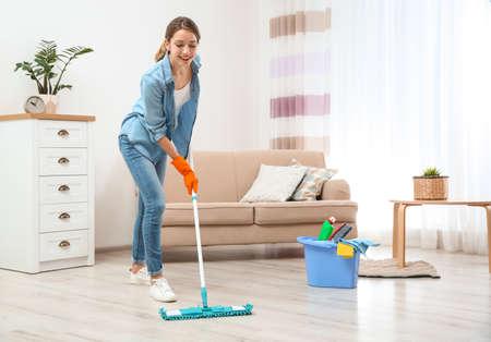 Mujer joven lavando el piso con un trapeador en la sala de estar. Servicio de limpieza Foto de archivo