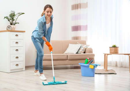 Young woman washing floor with mop in living room. Cleaning service Archivio Fotografico
