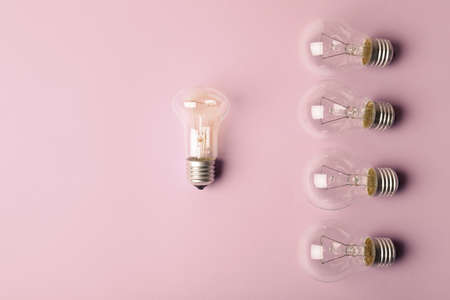 One different light bulb standing out from others on color background, top view