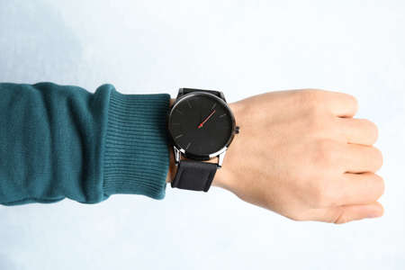 Man with stylish wrist watch on color background, closeup. Time management