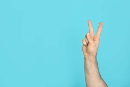 Young man showing victory gesture on color background. Space for text