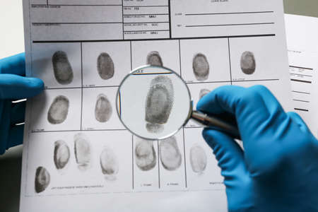 Criminalist exploring fingerprints with magnifying glass, closeup