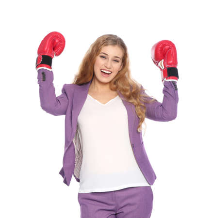 Happy young businesswoman with boxing gloves celebrating victory on white background