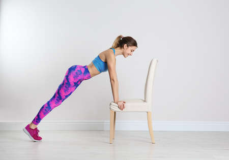 Young woman exercising with chair near white wall. Home fitness 版權商用圖片