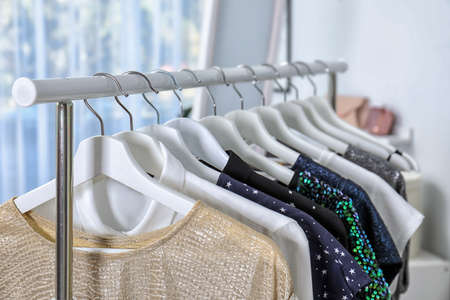 Stylish clothes hanging on wardrobe rack indoors, closeup
