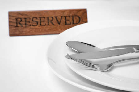 Elegant table setting and RESERVED sign in restaurant, closeup Foto de archivo