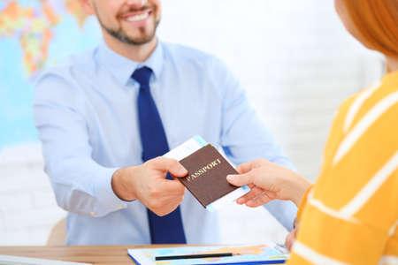 Mężczyzna kierownik daje paszport z biletem klientowi w biurze podróży, zbliżenie