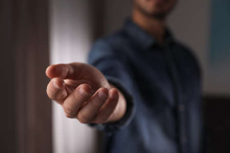 Man offering helping hand on blurred background, closeup