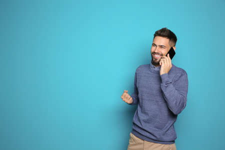 Happy young man with smartphone celebrating victory on color background. Space for text
