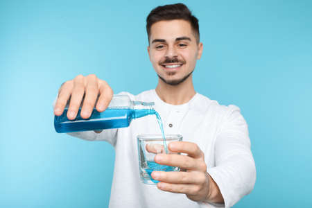 Young man pouring mouthwash from bottle into glass on color background. Teeth and oral care