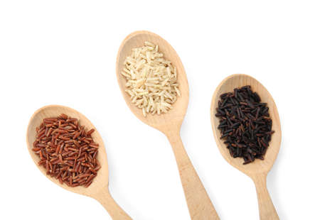 Spoons with different types of rice on white background, top view