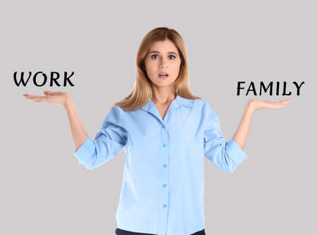 Woman finding balance between work and family on light background. Life harmony Stock fotó