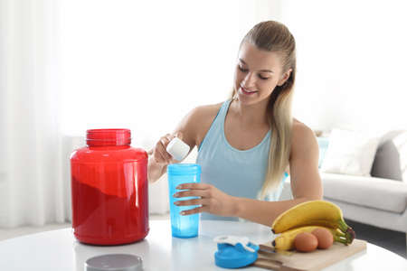 Young woman preparing protein shake at table in room 写真素材 - 114844635
