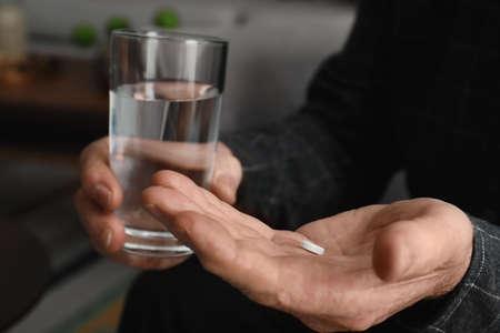 Älterer Mann mit Pille und Glas Wasser drinnen, Nahaufnahme